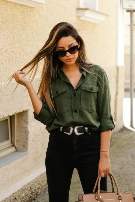 Girl wearing black jeans, with belt, sunglasses, and an army green tufted shirt