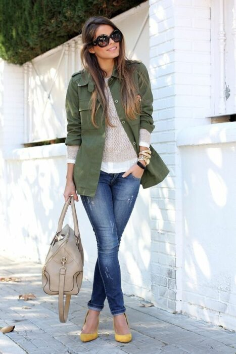 Girl wearing heels, jeans and a white blouse matching an army green blazer and a beige handbag