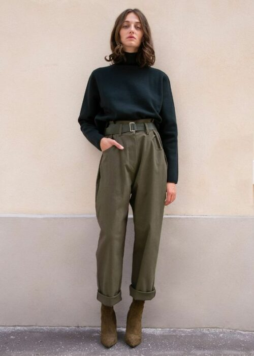 Girl wearing brown ankle boots, black turtleneck sweater with army green paper pants
