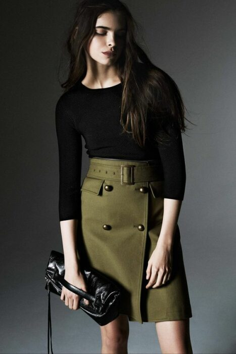 Girl wearing a black three-quarter sleeve blouse, with a handbag of the same color and an army green mini skirt