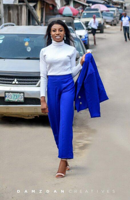 Chica llevando traje azul rey, caminando por la calle y clebrando su graduación; Vivía en edificios sin terminar, no tenía recursos, pero logró graduarse con honores