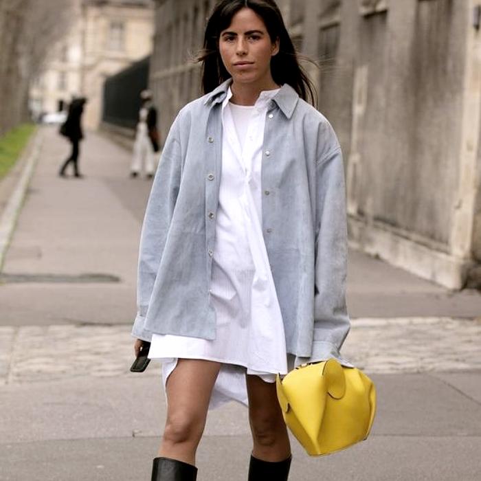 chica de cabello castaño usando un vestido blanco, camisa gris de botones, botas largas negras de cuero, bolso amarillo de mano