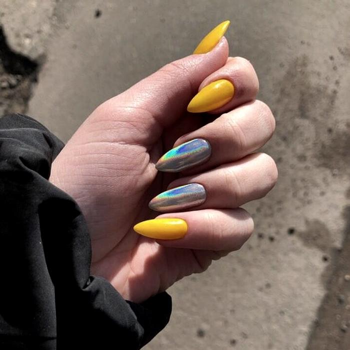 uñas largas acrílicas con esmalte amarillo y plateado con brillo