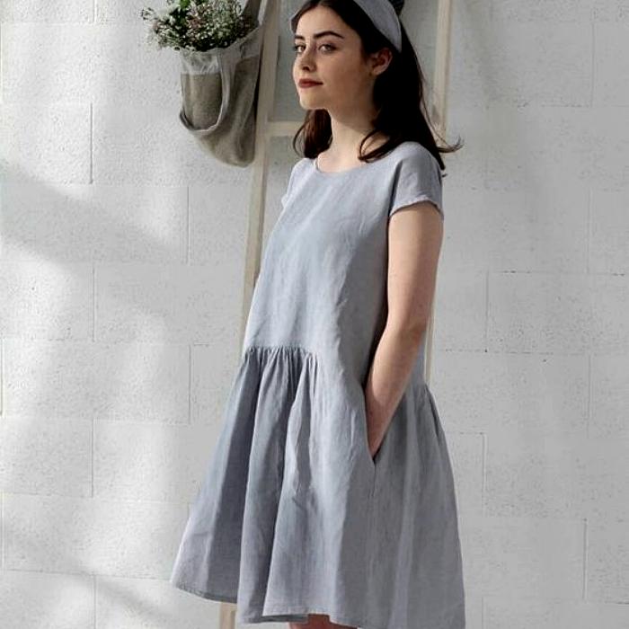 chica de cabello castaño usando un vestido largo color gris con manga corta y vuelo en la falda