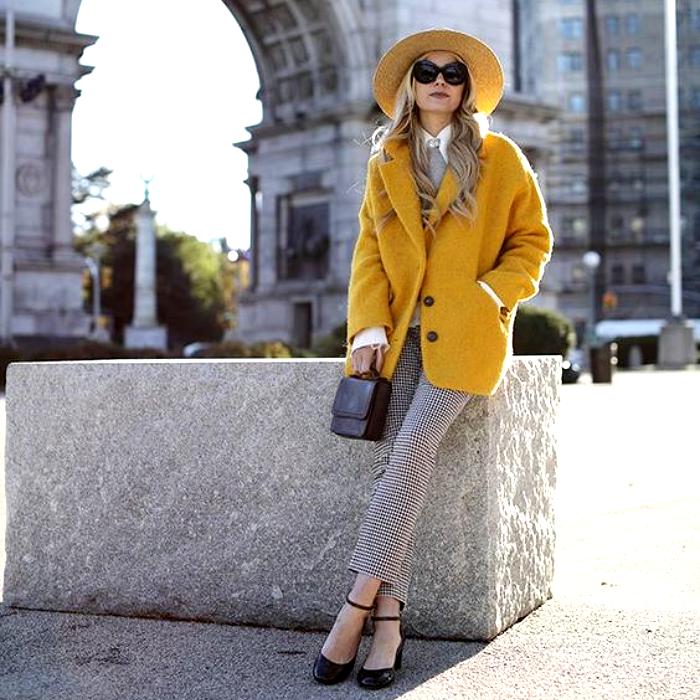 chica rubia con sombrero amarillo, lentes de sol negros, abrigo amarillo, pantalones blancos con gris, zapatos de tacón negros, bolso de mano negro, camisa blanca