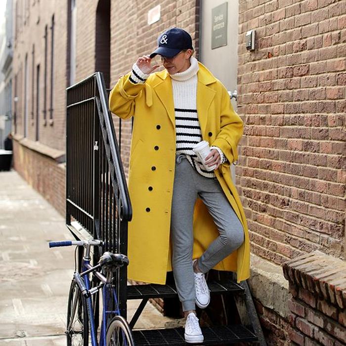 chica de cabello rubio usando una gorra azul, abrigo largo amarillo, suéter blanco con rayas negras, pantalones grises, tenis blancos