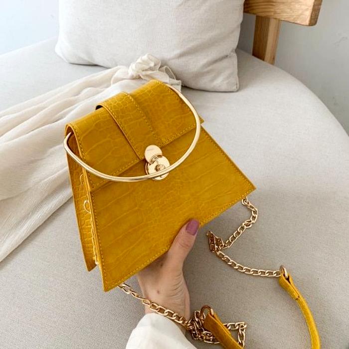 bolso amarillo con asa de metal dorada y correa amarilla larga