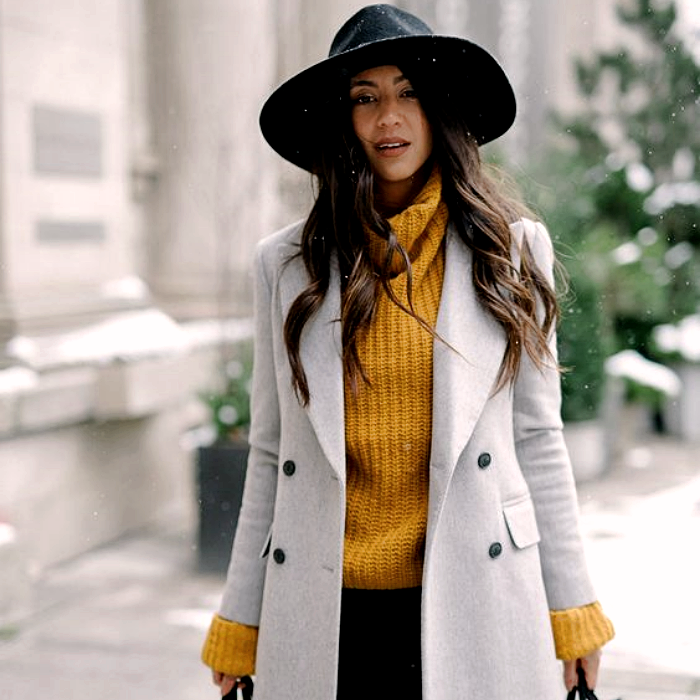 chica de cabello castaño largo usando un sombrero negro, suéter amarillo de cuello alto, abrigo largo gris, pantalones negros de mezclilla