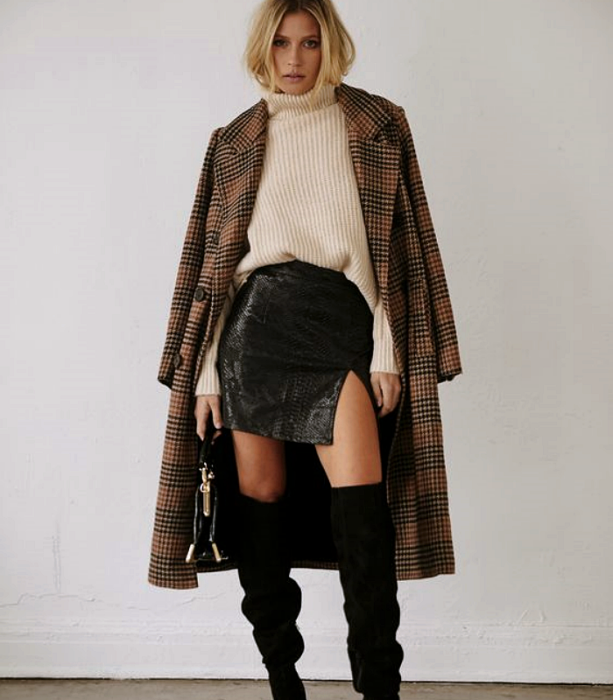 blonde haired girl wearing beige turtleneck sweater, long brown plaid coat, short leather skirt, black long boots