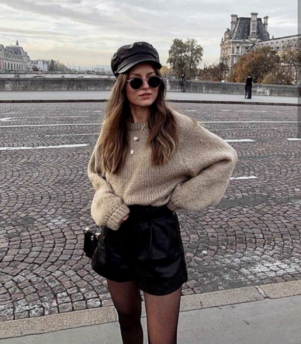 long light hair girl wearing sunglasses, black leather hat, baggy beige sweater, black leather shorts, black tights