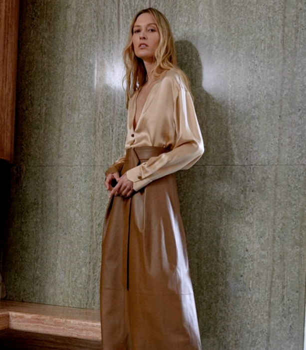 blonde girl wearing beige silk blouse, long light brown leather skirt
