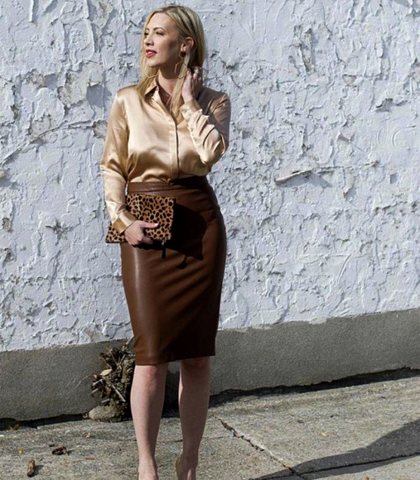 blonde girl wearing beige silk shirt, brown leather skirt, brown tote bag