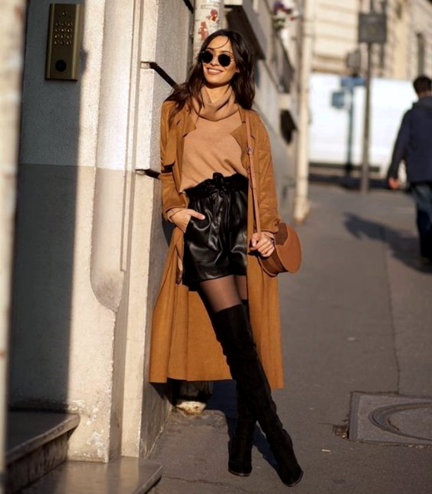 brown haired girl wearing sunglasses, brown turtleneck sweater, black leather shorts, black long boots, long brown coat, black stockings