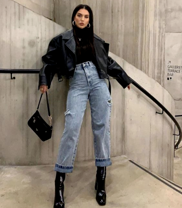 black haired girl wearing black top, baggy waist jeans, black heeled ankle boots, black tote bag