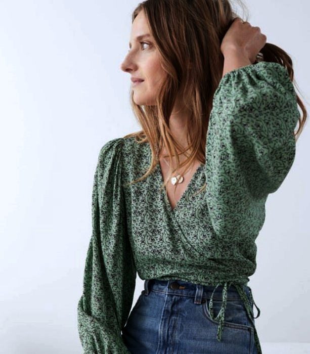 light haired girl wearing green blouse with baggy sleeves, V neckline, waist jeans