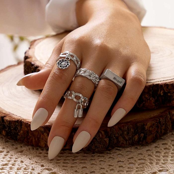 anillos plateados de diferentes diseños, manicura, uñas pintadas de color blanco mate