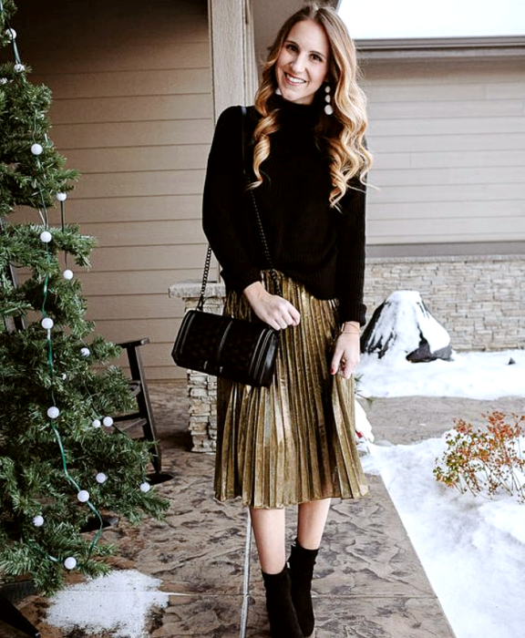 blonde girl wearing black knitted sweater, metallic gold long skirt, black ankle boots and black leather handbag