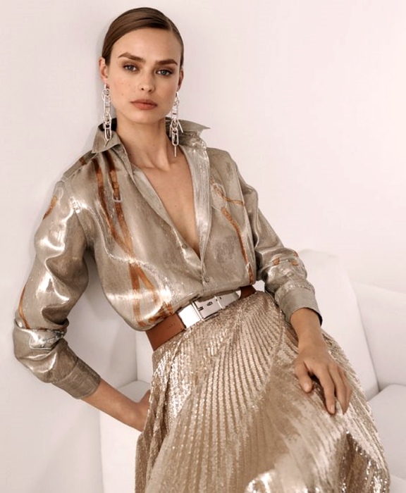 brown haired girl wearing metallic gold blouse with V neckline, long sleeves and dress collar, metallic champagne gold long skirt with planks