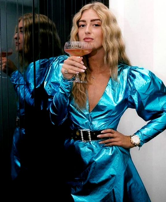 blonde girl wearing blue metallic dress with puff sleeves, black belt and oversized shoulder pads