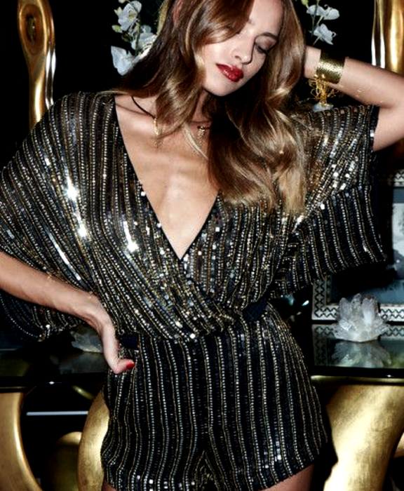 light haired girl wearing a black bodysuit with gold metallic lines, V neckline and short sleeves