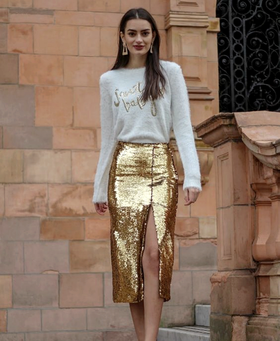 brown haired girl wearing white blouse with gold, metallic gold skirt with leg opening