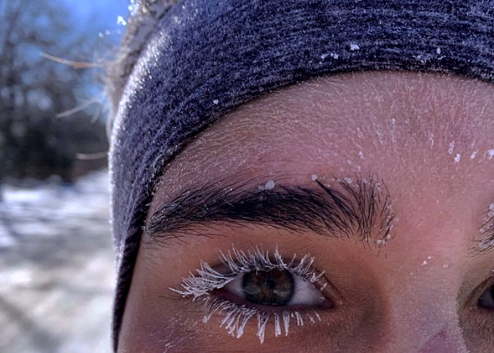pestañas de una chica, congeladas por el frío, rodeada de nieve