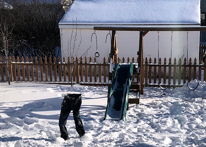 pantalones de mezclilla congelados en el jardín, rodeado de nieve por el frío
