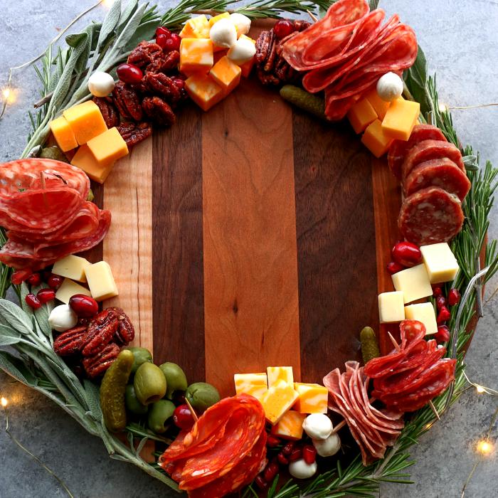 tabla de quesos, embutidos, charcutería, uvas, salami, jamón serrano, con estilo navideño