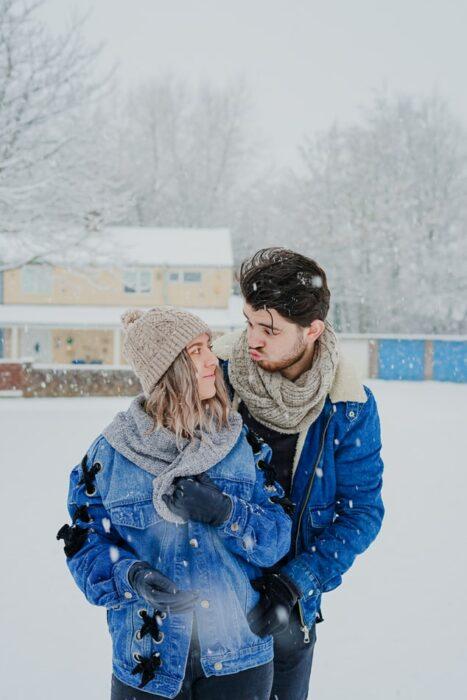 Pareja en el exterior un día nevado de invierno