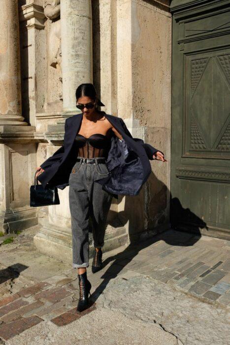chica con pantalones de mezclilla holgados combinado con top negro; 13 Ideas para usar pantalones holgados sin perder el estilo