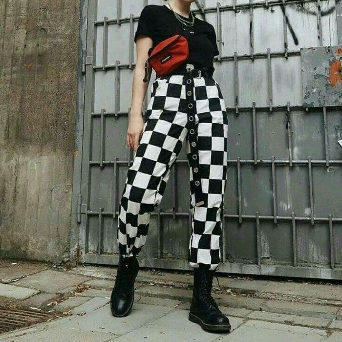 Chica con pantalones holgados a cuadros en color blanco y negro; 13 Ideas para usar pantalones holgados sin perder el estilo