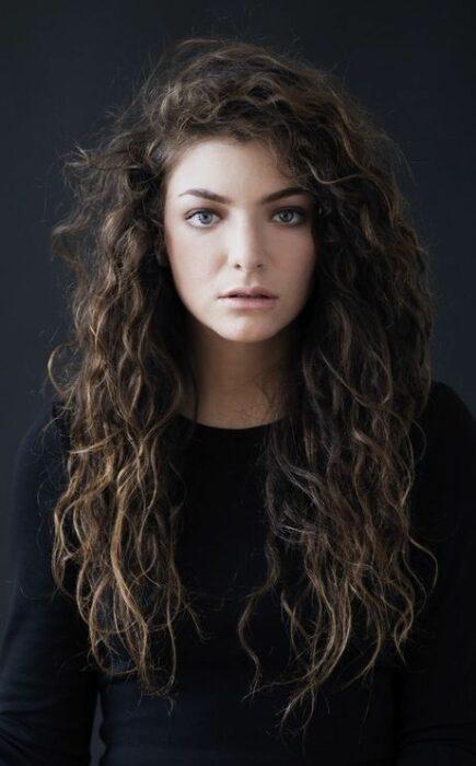 Lorde posando para una foto, llevando suéter negro con cabello largo rizado