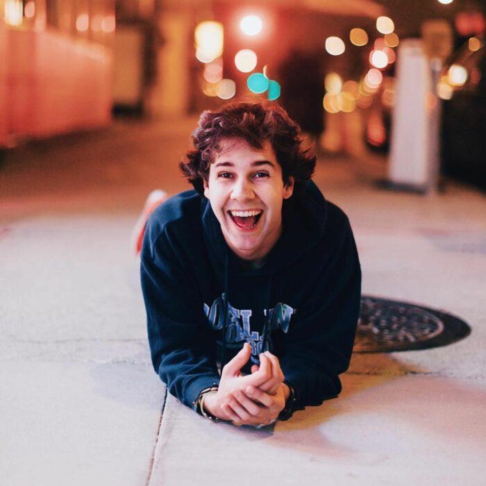 David Dobrik sonriendo, recostado en el piso para una fotografía de noche