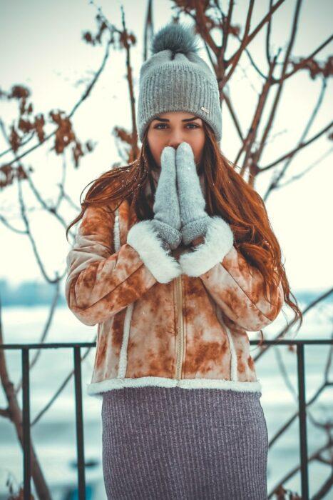 Chica usando prendas de invierno en un día nevado