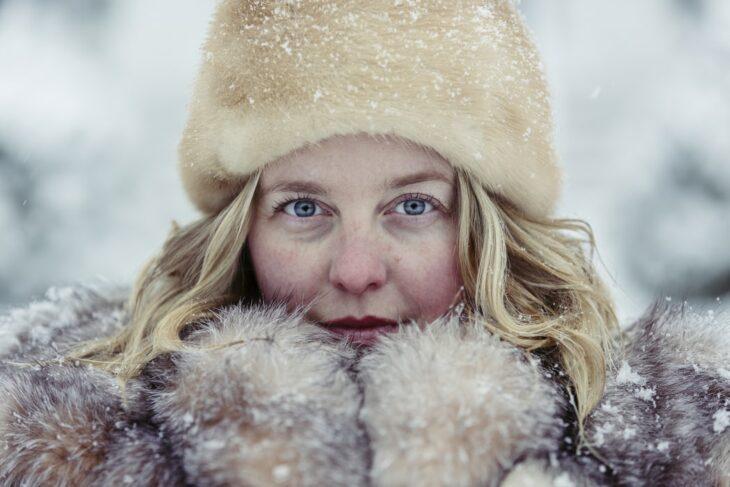 Mujer usando prendas de invierno en un día nevado