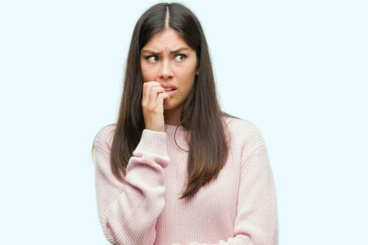 Chica mordiéndose las uñas; 4 Motivos por los que podrías morder tus uñas constantemente