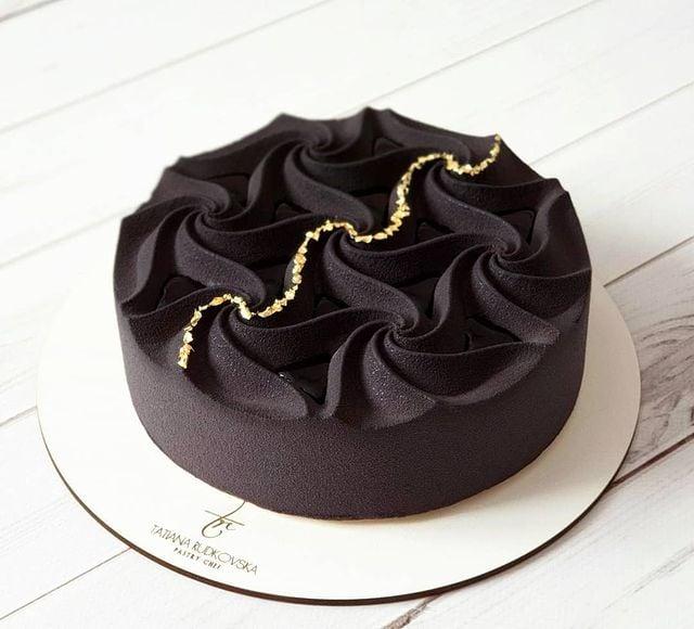 Pastel de un piso con betún negro y decorado en dorado