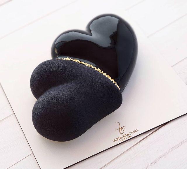 Pastel de chocolate en forma de corazón con betún negro y decoraciones en dorado