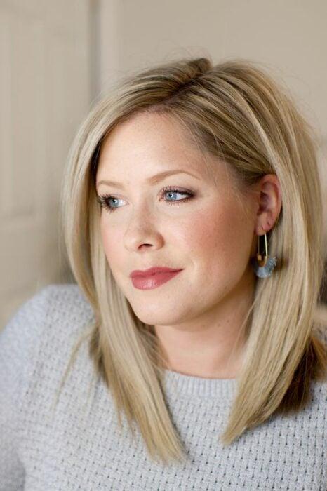 Mujer rubia con suéter gris con cabello en melena media