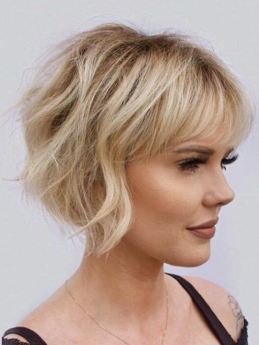 Blonde woman in profile with very short slightly curly hair