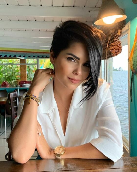 Woman sitting in white blouse with pixie style hair with a longer side