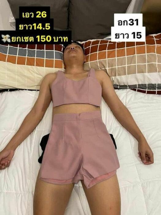 Hombre dormido llevando un traje de dos piezas en rosa palo; Mujer utiliza a su esposo dormido como maniquí para vender ropa en línea
