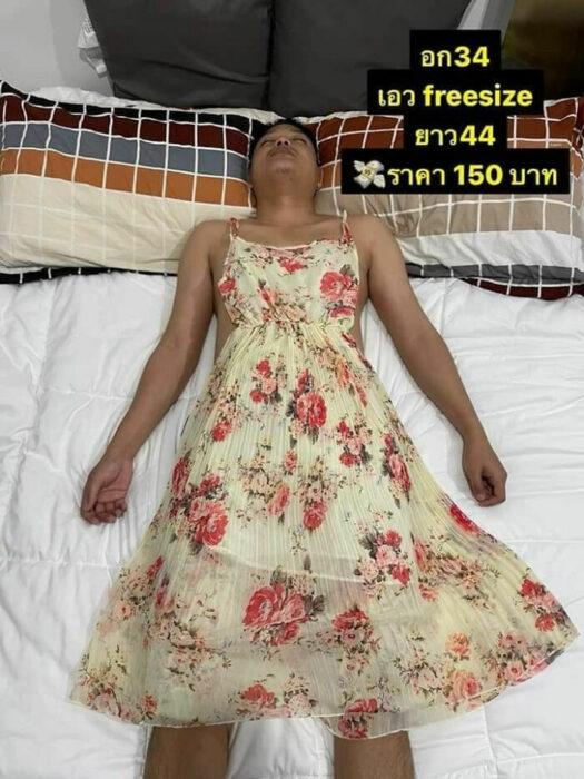 Hombre recostado llevando vestido de tirantes con flores; Mujer utiliza a su esposo dormido como maniquí para vender ropa en línea