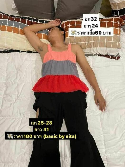 Hombre dormido llevando un traje de dos piezas con blusa de colores y pantalón negro sobrepuesto; Mujer utiliza a su esposo dormido como maniquí para vender ropa en línea