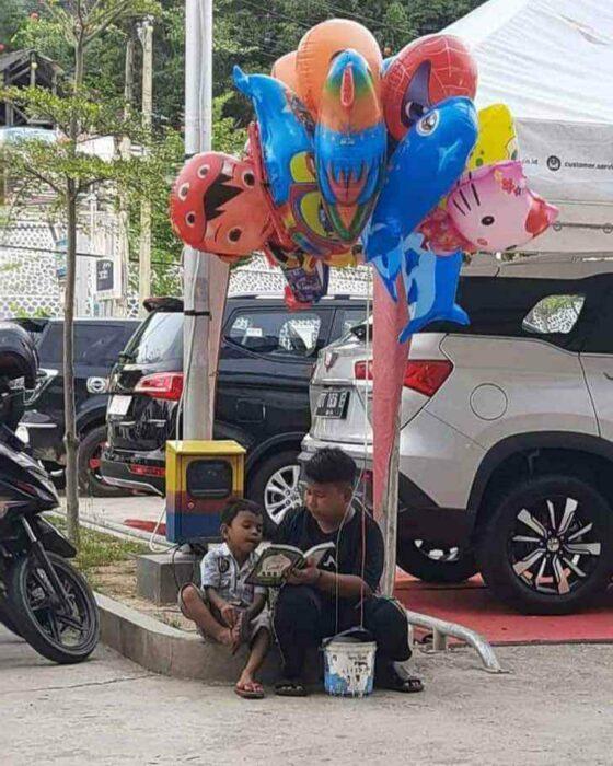 Niño le enseña a leer a su hermanito en la calle