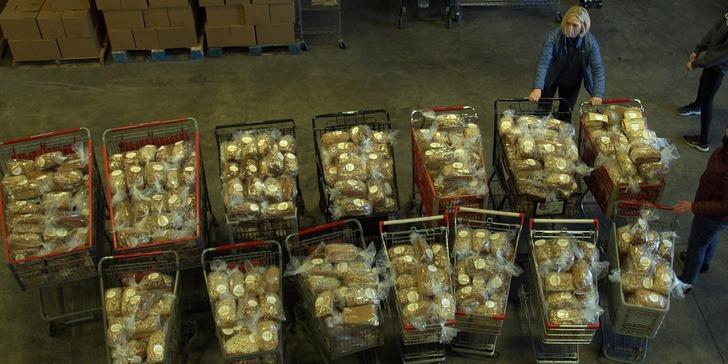 Chica con carros de supermercado rellenos de pan artesanal