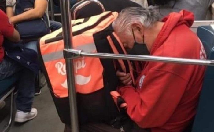 Panchito sentado en el metro, llevando su mochila de Rappi