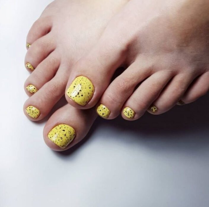 Pedicure in yellow colors with black dotted details