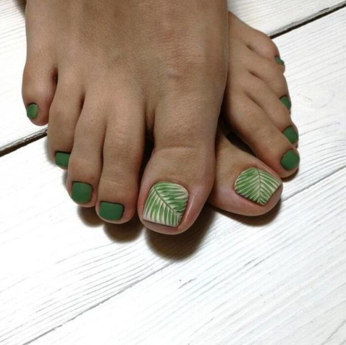 Pedicure in green colors with palm leaf details