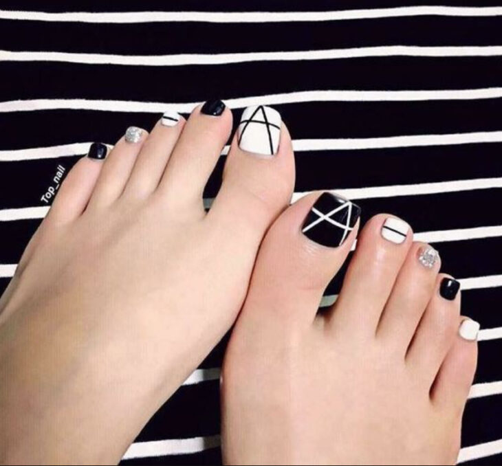 Pedicure in black and white colors with line details
